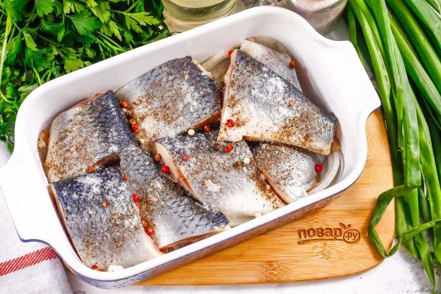 Посолите и поперчите кусочки рыбы с обеих сторон, высыпьте горошины черного перца.