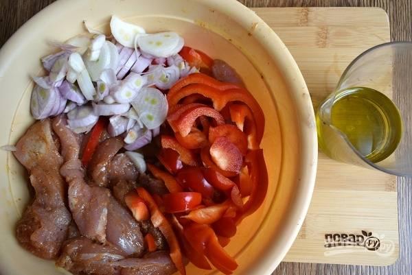 Мясо нарежьте небольшими полосками, добавьте специи и масло, нарезанный  полосками болгарский перец и лук. Аккуратно перемешайте  и оставьте  на 30 минут.