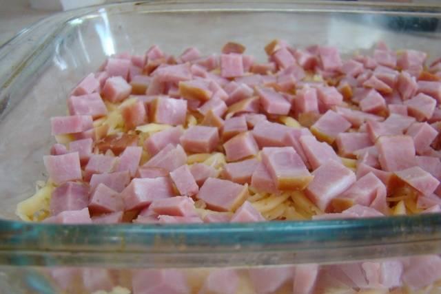 Ветчину нарезаем на маленькие кубики и выкладываем поверх сыра.