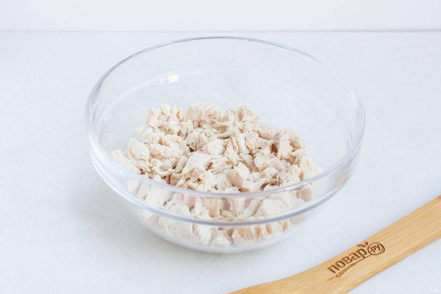 Куриное филе нарежьте кубиками и выложите первым слоем салата. Смажьте майонезом или нанесите майонезную сеточку.
