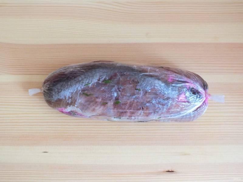 Аккуратно сверните рыбу в рулет, не позволяя вылезти начинке. Закрутите концы пищевой пленки. Уберите рулет в холодильник на 2 часа.
