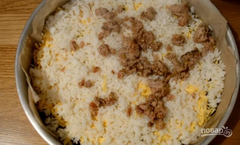 7. Поверх риса укладываем обжаренный с луком мясной фарш, распределяем.