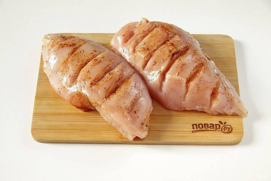 В курином филе сделайте глубокие поперечные надрезы. Натрите филе солью и специями.