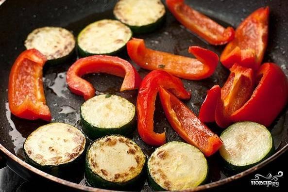 1. Нарезать кабачки ломтиками, полукругом или четвертинками толщиной 0,5-0,7 см. Нарезать сладкий перец соломкой. Обжарить овощи в растительном масле в сковороде.