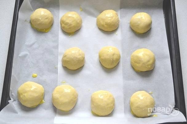 13. Выложите булочки на противень, застеленный пергаментом, смажьте желтком и отправьте в разогретую до 180 градусов духовку.