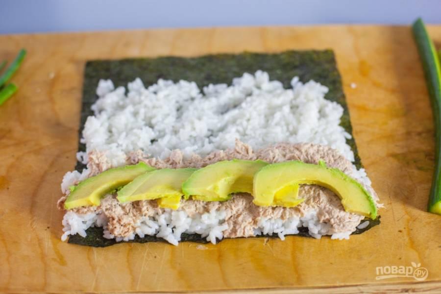 3.Очистите авокадо и нарежьте его тонкими полукольцами, выложите на суши.