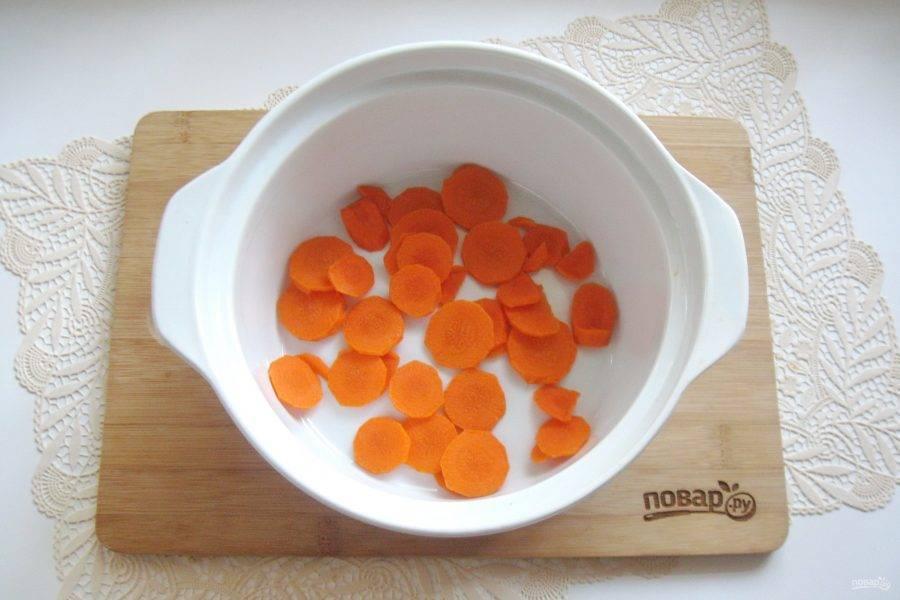 Морковь очистите, помойте и нарежьте произвольно. Я нарезала кружками. Так морковь выглядит аппетитнее в готовом блюде. Выложите морковь в жаропрочную форму.