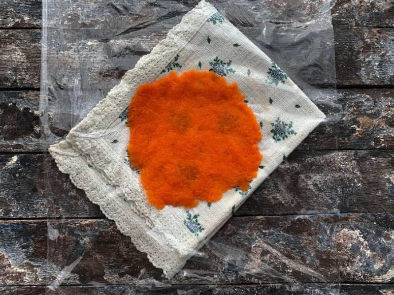 На пищевую пленку выложите небольшое количество моркови и распределите ее тонким слоем.