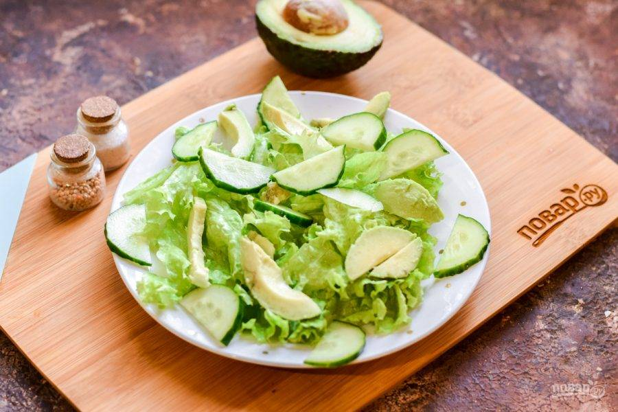 На листья выложите авокадо и огурцы.