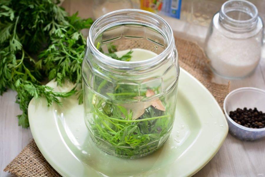 Выложите на дно стерилизованной банки вымытую морковную ботву, перец горошком и лавровый лист.