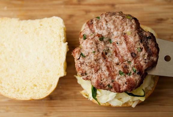 Теперь собираем наши бургеры. Разрежьте булочку поперек. На нижнюю половину положите часть капусты, на нее свиную котлету, которую полейте рыбным соусом.