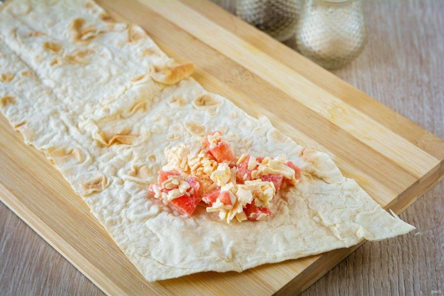 Нарежьте лаваш на полоски шириной 6-7 см., длиной около 15 см. На один край выложите ложку начинки.