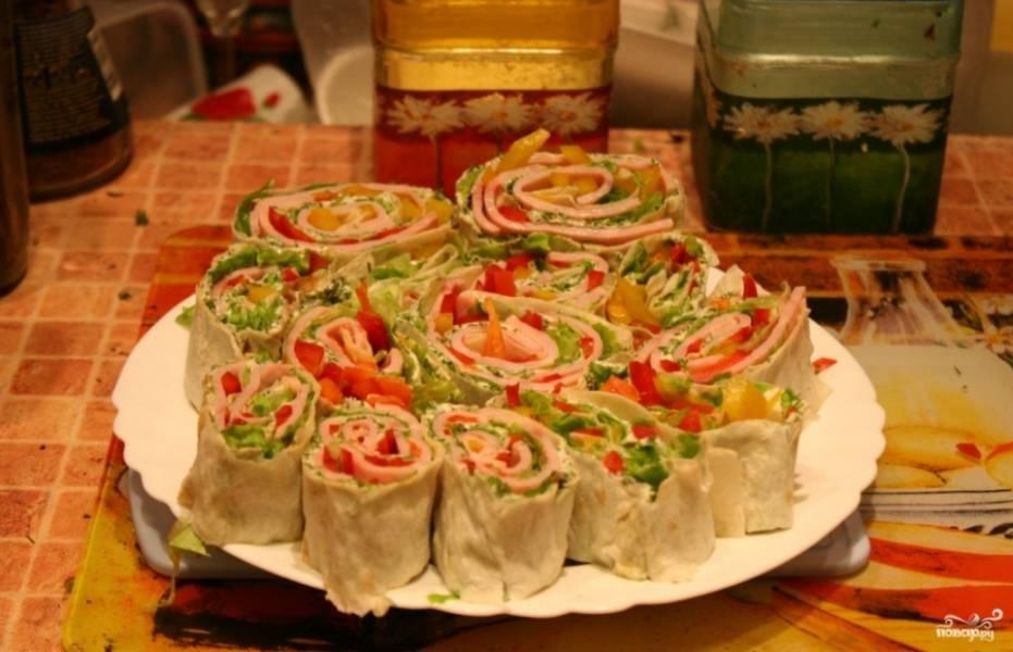 Перед подачей готовый лаваш с ветчиной и сыром порежьте на порционные кусочки. Можете подавать его к столку с томатным или сырным соусами. Приятного аппетита!