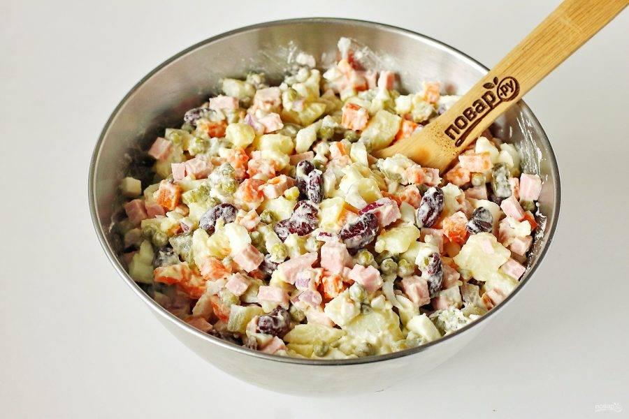 Заправьте салат майонезом, добавьте по вкусу соль и все хорошо перемешайте. Оливье с фасолью готов.