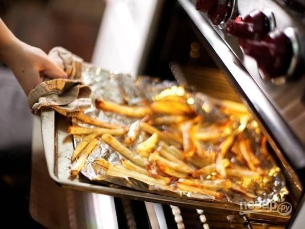 Потом отправьте высушенный картофель на противень. Добавьте соль, масло и перец. Запекайте картошку при 200 градусах около 30 минут.