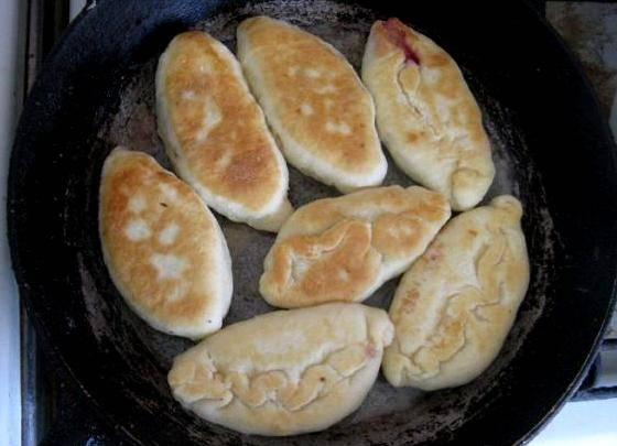 Теперь наливаем на сковороду растительное масло и нагреваем его. Выкладываем пирожки на сковороду швом вниз и обжариваем их с каждой стороны до румяной корочки.