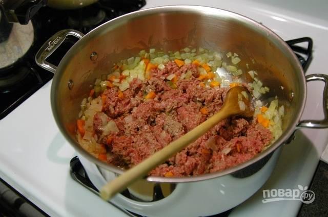 8.Увеличьте огонь и выложите к овощам мясной фарш, хорошенько разомните его ложкой.