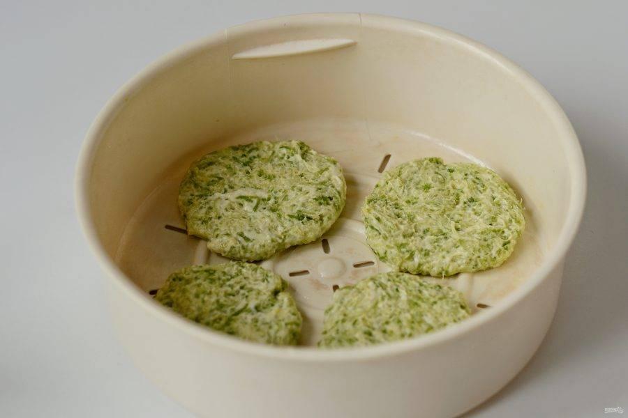 Смажьте форму, в которой будете готовить оладушки, растительным маслом. Мокрыми руками сформируйте небольшие котлетки. Выложите их на небольшом расстоянии друг от друга. Готовьте оладьи на пару 15 минут.