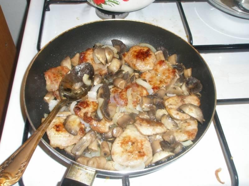 Добавьте к луку порезанные грибы и обжаренное мясо. Влейте немного воды и тушите под крышкой 15 минут.