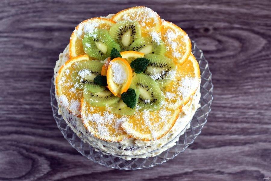 Пропитанный торт украсьте сверху свежими тропическими фруктами по вкусу, тонко их нарезав. Можно припорошить торт кокосовой стружкой.