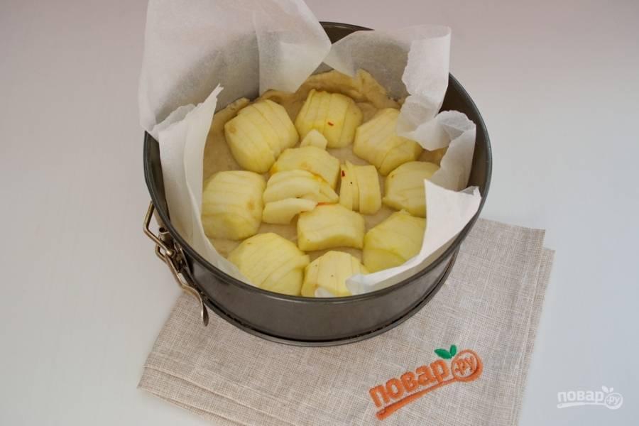 Очистите яблоки от шкурки и сердцевины, нарежьте каждую половинку яблока на дольки. Уложите яблоки на тесто половинками.