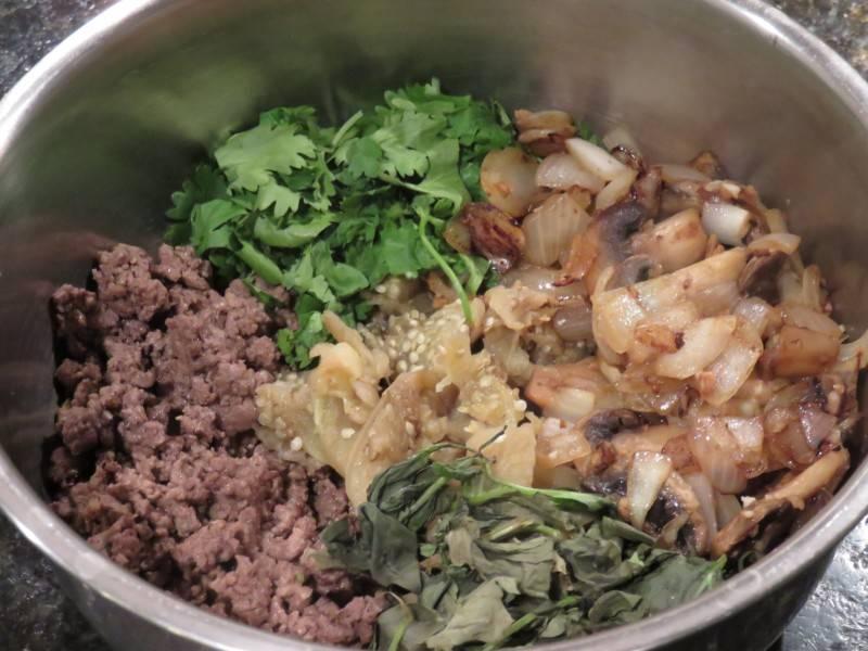 Смешайте в миске фарш, грибы, зелень, отваренную мякоть баклажана, специи. Хорошо размешайте.