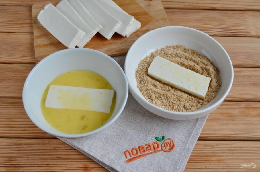 Каждый ломтик сыра окуните в яйцо, после — в смесь сухарей и кунжута.