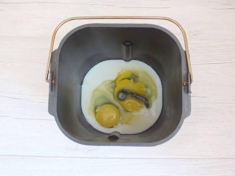 В ведерко хлебопечки налейте теплое молоко, добавьте 2 яйца.