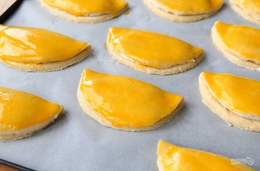 6.Заверните сочники, смажьте их сверху яичным желтком. Выпекайте в разогретой до 200 градусов духовке 15 минут.