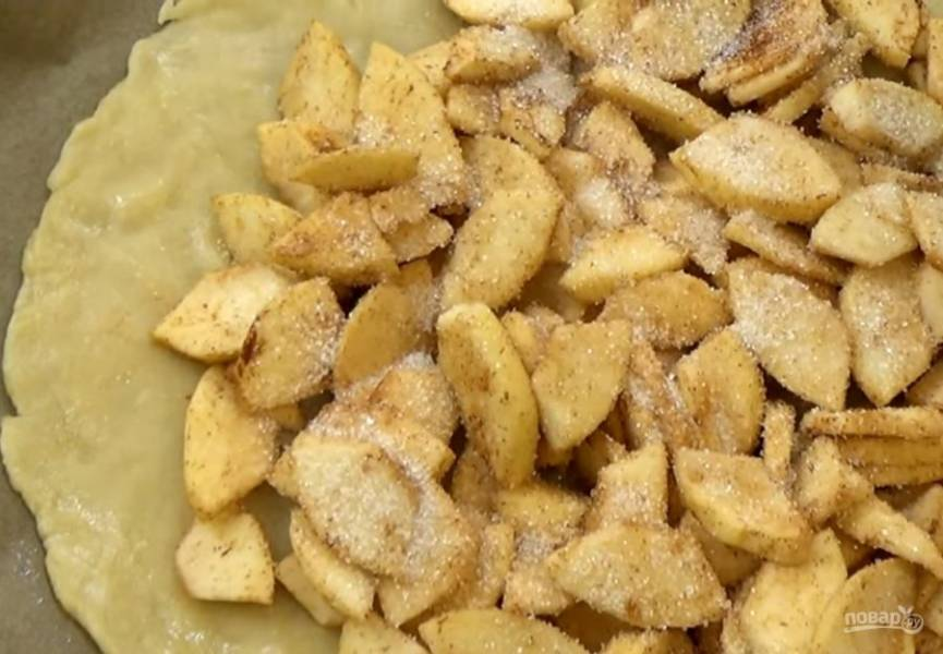 3. По центру выложите яблоки, посыпьте сахаром, заверните и защипните края теста. Отправьте пирог в разогретую до 190 градусов духовку на 40 минут.