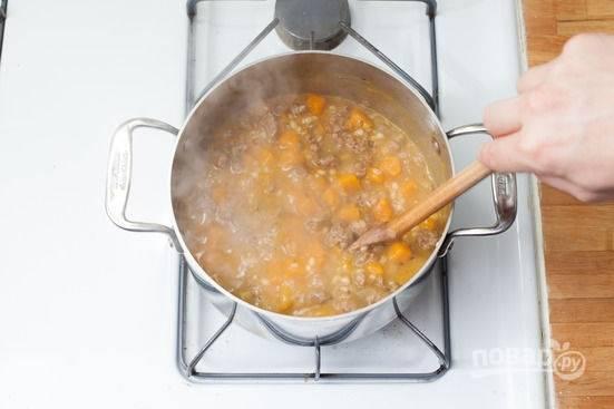 3.Добавьте тыкву, перловку, тимьян и залейте все 3 стаканами воды. Варите все на среднем огне около 15 минут. Уберите кастрюлю с огня.
