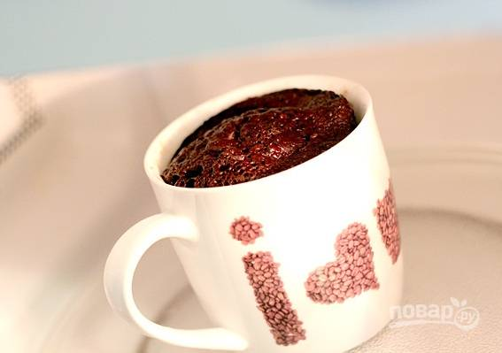 Поставьте чашку в микроволновую печь приблизительно на 2-3 минут при мощности 700W.  Не переживайте, когда тесто начнет выходить из чашки, после открытия печь кекс осядет.   В конце вытяните кекс из микроволновки, посыпьте сахарной пудрой и наслаждайтесь!