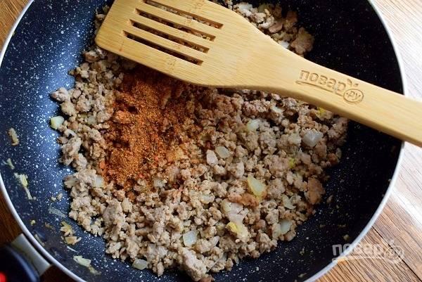 """Пока отвариваются макароны, на разогретой сковороде обжарьте фарш до румянца, добавьте измельченный лук, перемешайте, обжарьте в течение 1 минуты. Добавьте приправу """"Тако"""", перемешайте."""