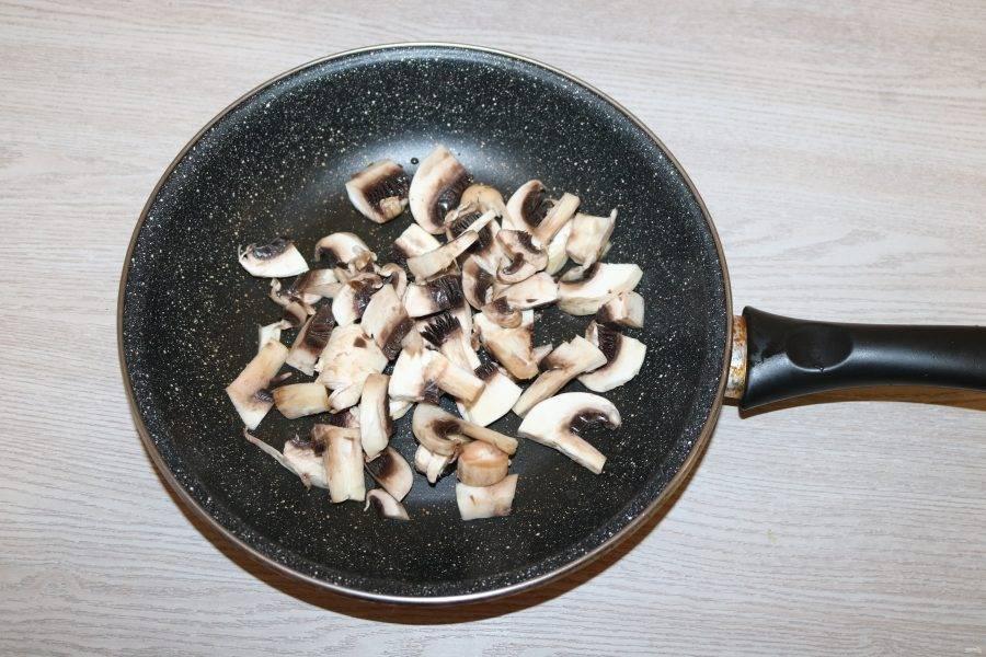 Шампиньоны нарежьте кусочками, обжарьте на разогретой сковороде с добавлением небольшого количества масла.