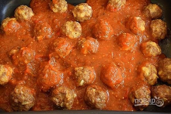 Залейте фрикадельки томатным соусом и запекайте еще 8-10 минут.