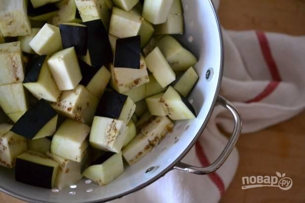 1.Вымойте баклажаны и нарежьте их небольшими кубиками, сложите все в дуршлаг или сито и посолите, оставьте на 15 минут.