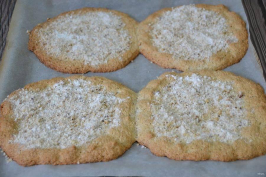 Посыпьте смесью сахарной пудры и орехов испеченные коржи. На этом можно считать, что дакуаз готов. Аккуратно снимите коржи с листа. Если не планируете их использовать сразу, можно завернуть в пищевую пленку.