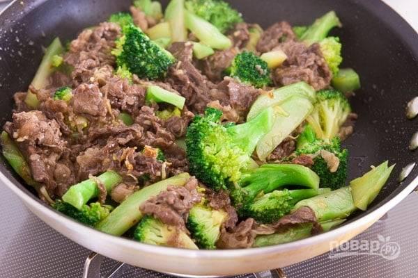 5.Откройте крышку и добавьте мясо, в отдельной емкости смешайте оставшийся крахмал с куриным бульоном, устричным соусом, молотым перцем, вылейте все в сковороду. Перемешайте все содержимое и готовьте несколько минут.