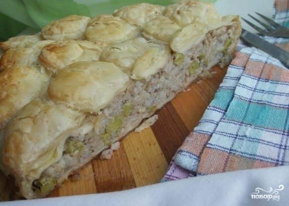 Подавайте пирог из слоеного теста с рыбными консервами в горячем виде.