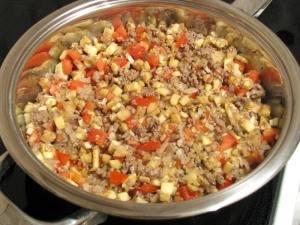 Помидоры и мякоть баклажанов режем кубиками и добавляем на сковороду. Солим и перчим по вкусу, жарим еще 7-8 минут, помешивая.