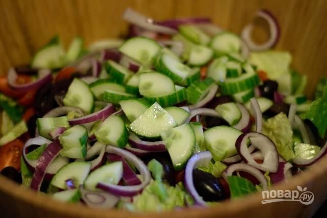 3. В глубоком салатнике соедините листья салата, огурчики, помидоры, лук, сладкий перец, маслины и сыр. Полейте заправкой и аккуратно перемешайте.