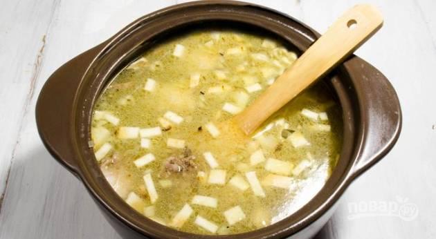 Перекладываем продукты со сковороды в кастрюлю с горячим бульоном, ставим на самый маленький огонь на 15 минут.