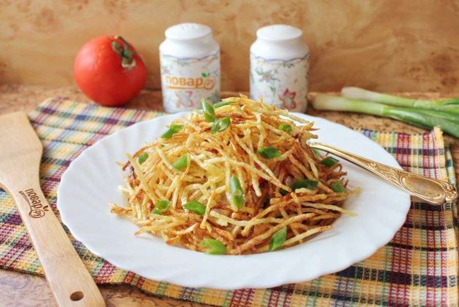 Покройте горку салата картофельной соломкой и посыпьте нарезанным зеленым луком. Можно подавать к столу.