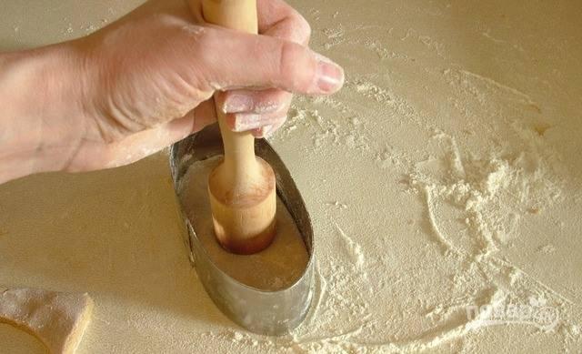 Поместите пряник в металлическую форму так, чтобы она обрезала неровные края теста. Затем деревянной колотушкой или пестиком прижмите его сверху, словно вдавливая начину.