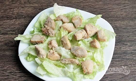 На тарелку для подачи нарвите промытые листья салата. Выложите кусочки курицы.