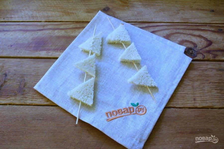 Батон белого хлеба нарежьте кусочками, срежьте корочки. Из мякоти нарежьте фигурные гренки. Оденьте их на бамбуковые палочки.