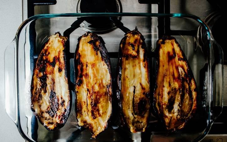 2. Выложить баклажаны мякотью вниз и отправить в разогретую духовку. В зависимости от размера, запекать баклажаны в карамели в домашних условиях от 15 до 25 минут. Вынуть их из духовки и переложить в жаропрочную форму подходящего размера.