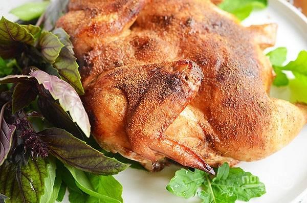 Разрежьте курицу вдоль грудки, выложите на противень, посыпьте молотым перцем и любимыми приправами. Запекайте в разогретой до 180 градусов духовке около 45 минут.