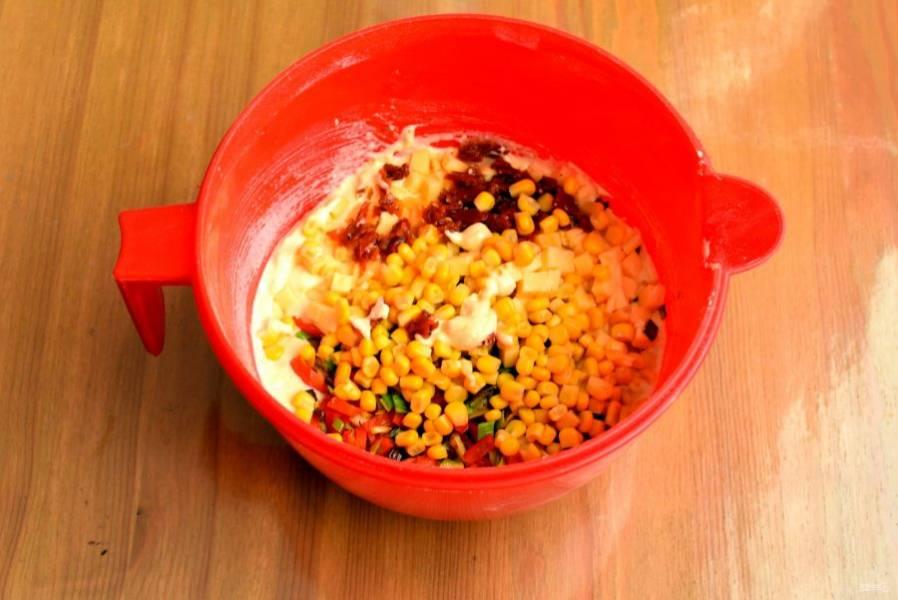 Выложите в тесто обжаренные овощи, натертый сыр, обсушенную от заливки кукурузу и вяленые помидоры. Всыпьте пряные травы и еще раз перемешайте тесто.