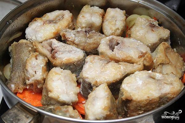 Теперь выкладываем обжаренные кусочки рыбы на оставленные в сковородке овощи. Сверху выкладываем вторую половину овощей. Огонь пока не включаем.